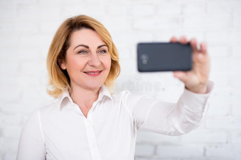 Stående av den gladlynta kvinnan för mogen affär som tar selfie med den smarta telefonen över den vita väggen arkivbild