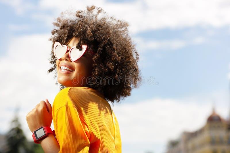 Stående av den gladlynta kvinnan i hjärta-formad solglasögon royaltyfri bild