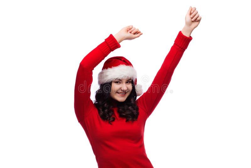 Stående av den gladlynta kvinnan som bär xmas-hatten som lyfter henne händer och dans som isoleras royaltyfria foton