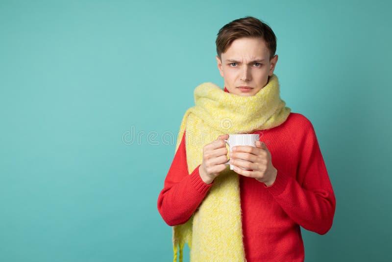 Stående av den gladlynta ledsna dåligt unga mannen i röd sweeater och den gula halsduken med koppen av varmt te royaltyfri fotografi