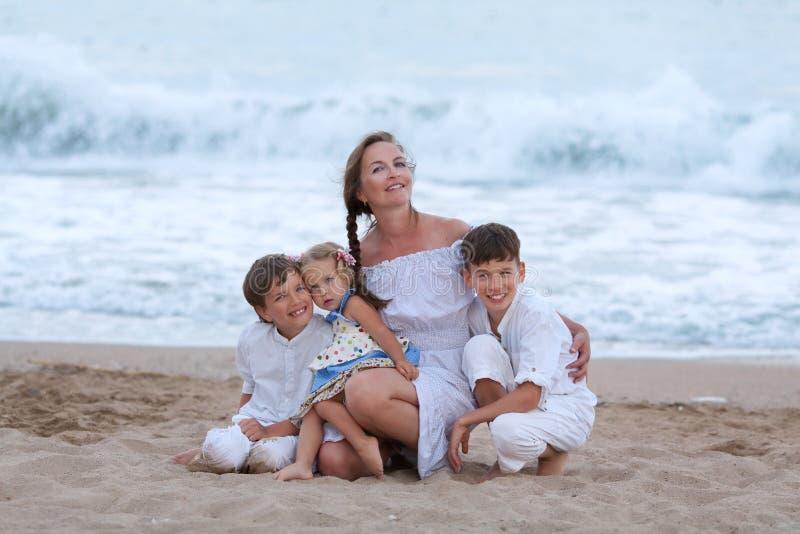Stående av den gladlynta lyckliga modern och söner på stranden arkivfoton