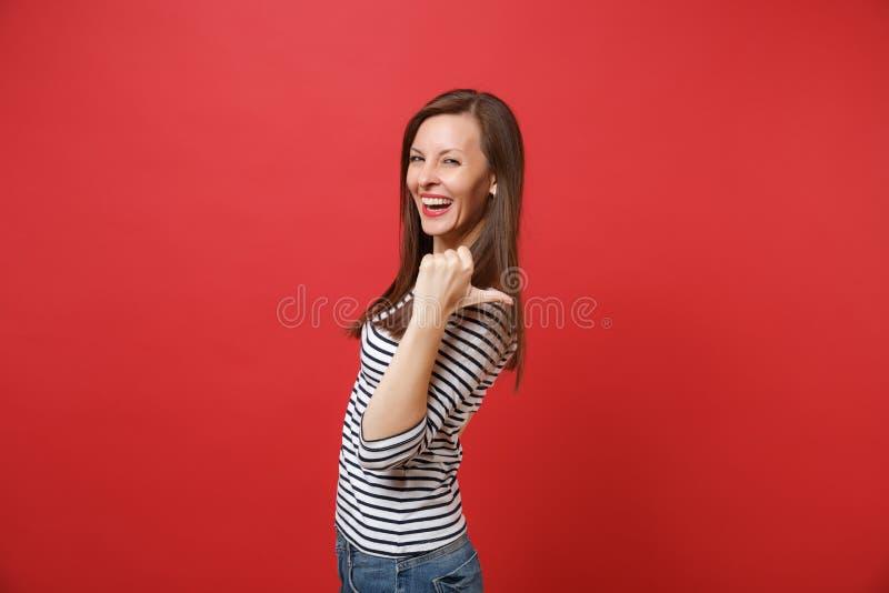 Stående av den gladlynta skratta unga kvinnan i randig kläder som pekar tummen bak hennes baksida som isoleras på den ljusa röda  royaltyfria foton
