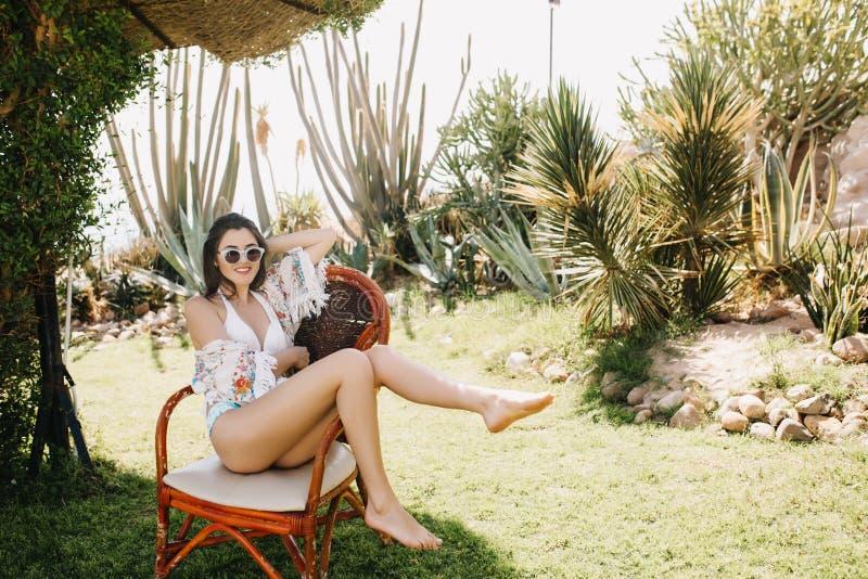 Stående av den gladlynta slanka flickan i solglasögon som har gyckel i gården med exotiska växter i solig dag F?rtjusande ungt royaltyfri foto