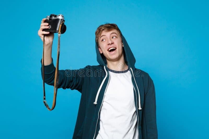 Stående av den gladlynta unga mannen i tillfällig kläder som gör selfie som skjutas på den retro tappningfotokameran som isoleras royaltyfria bilder