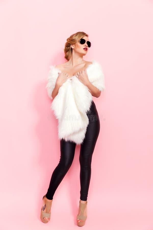 Stående av den glam flickan i vit päls och solglasögon på rosa bakgrund royaltyfria foton