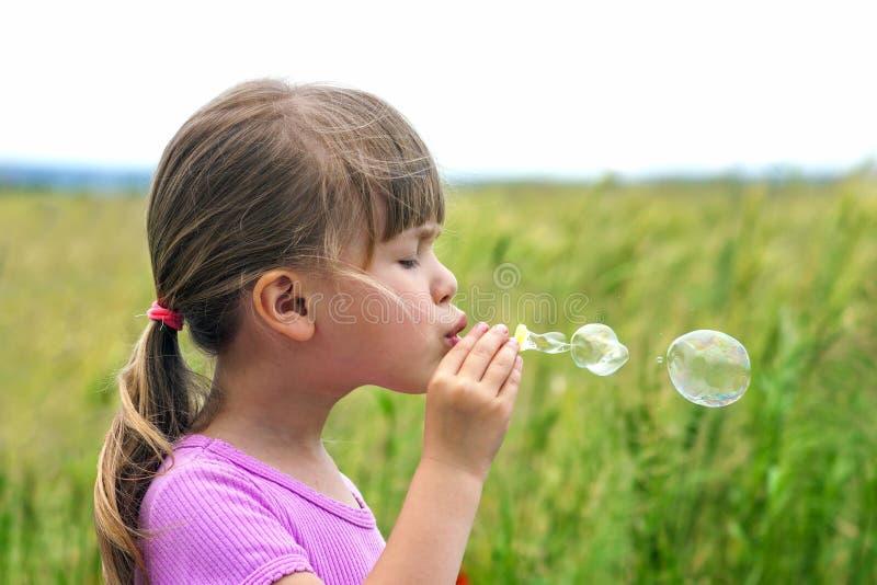 Stående av den gulliga älskvärda lilla flickan som blåser såpbubblor arkivbild