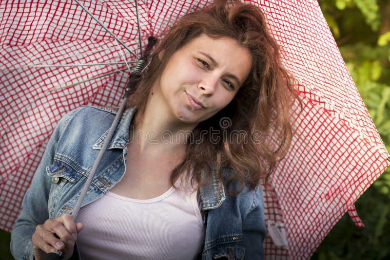 Stående av den gulliga attraktiva flickan med paraplyet Härligt anseende för ung kvinna under ett paraply efter regn på solig aft arkivbilder