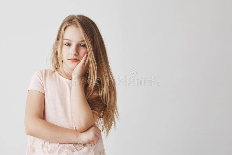 Stående av den gulliga blonda lilla flickan i rosa t-skjorta hållande huvud med handen, tröttas och borrat under skolagrupper royaltyfri foto