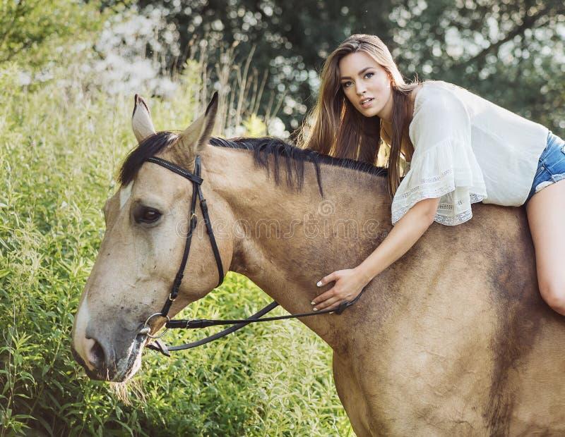 Stående av den gulliga brunettkvinnan som rider en häst arkivbilder