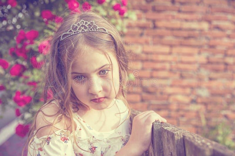 Stående av den gulliga flickan bredvid ett trästaket och härliga blommor arkivfoto