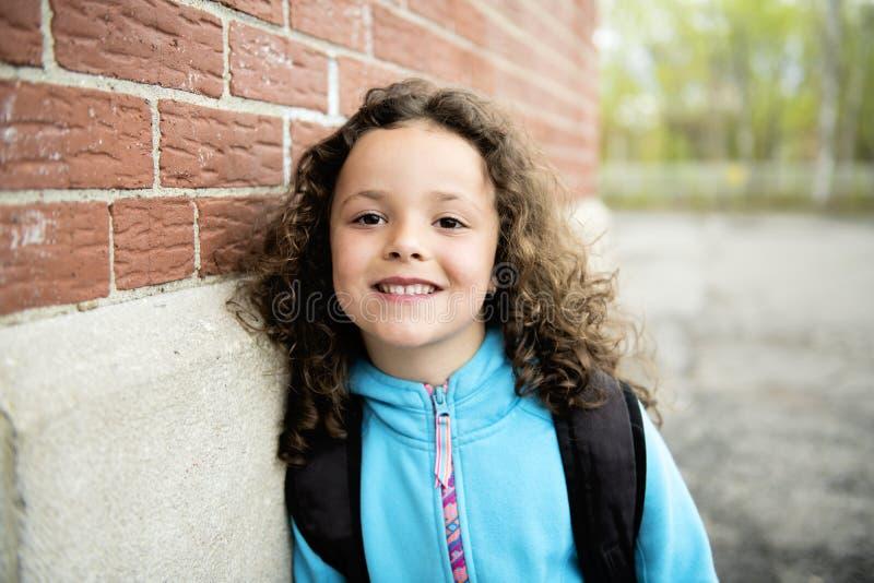 Stående av den gulliga flickan med skolan för ryggsäck förutom arkivbilder
