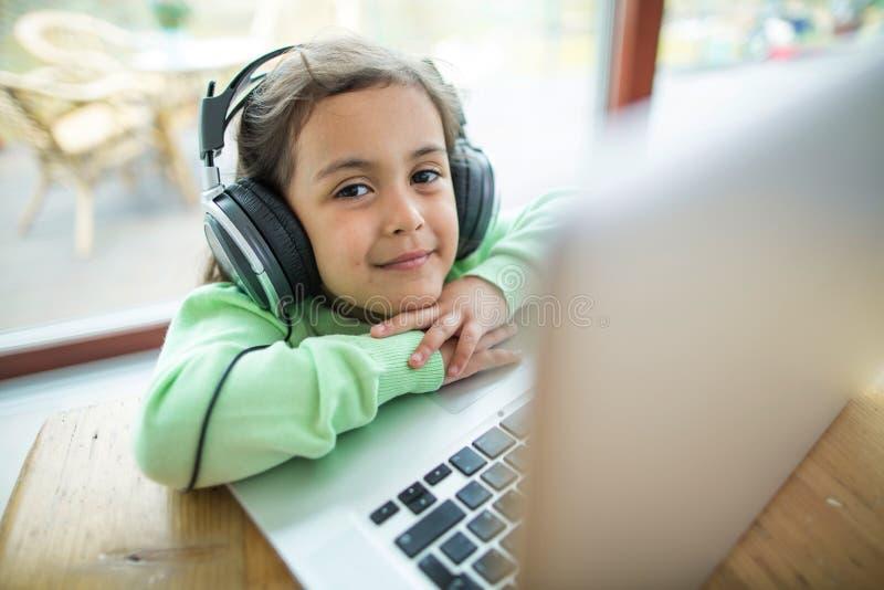 Stående av den gulliga flickan som lyssnar till musik på hörlurar med bärbara datorn på tabellen arkivbilder