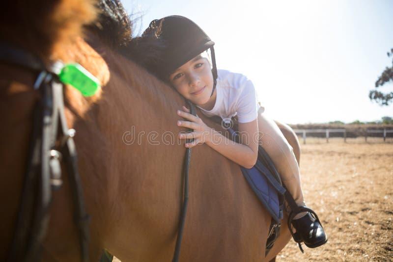 Stående av den gulliga flickan som omfamnar hästen i ranchen royaltyfria foton