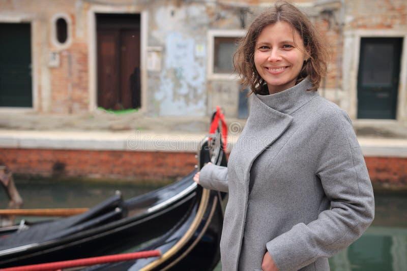 St?ende av den gulliga kvinnan mot gondolen i Venedig, Italien Lopp till Venezia Flicka i den Venedig kanalen med gondoler Lyckli royaltyfri foto