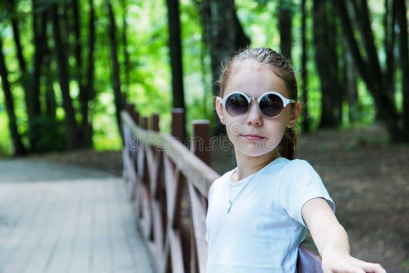Stående av den gulliga le flickan i skogen i solglasögon arkivbilder