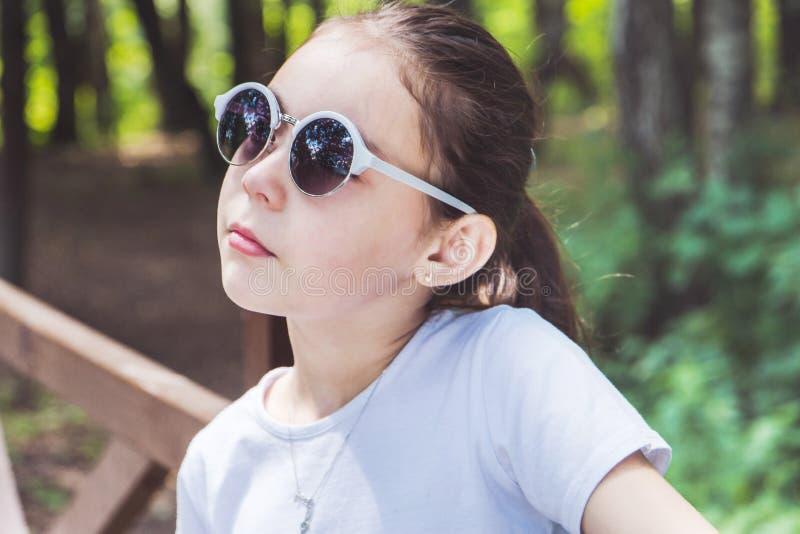 Stående av den gulliga le flickan i skogen i solglasögon royaltyfria bilder
