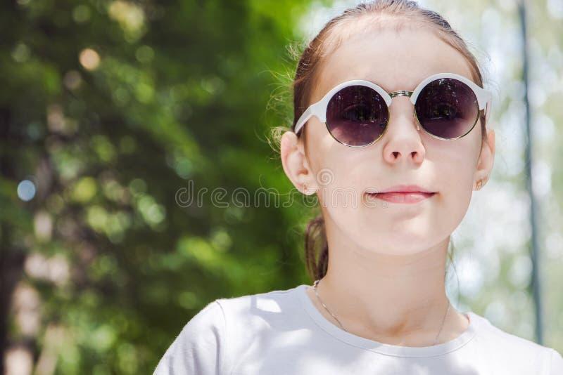 Stående av den gulliga le flickan i skogen i solglasögon tätt upp royaltyfri bild