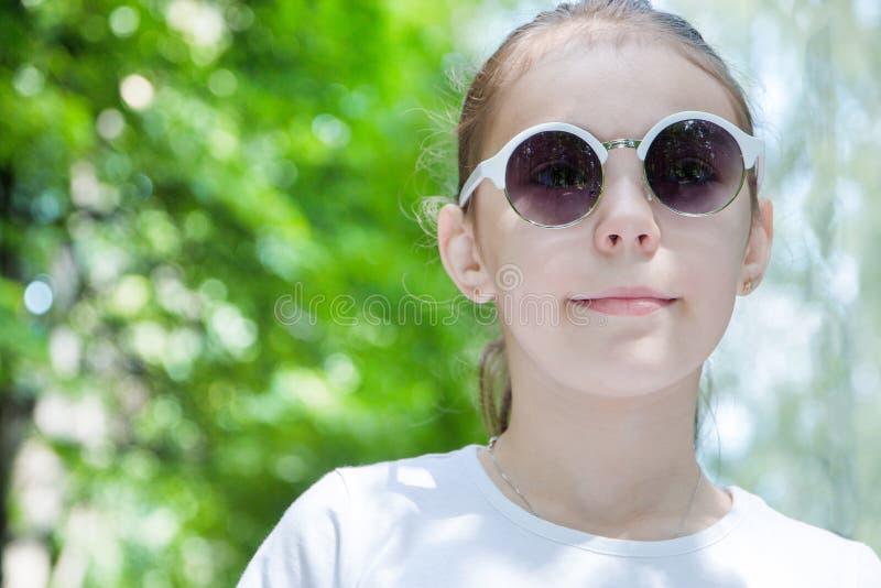 Stående av den gulliga le flickan i skogen i solglasögon tätt upp arkivfoto