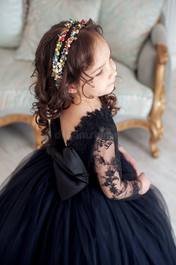 Stående av den gulliga le lilla flickan i fluffig klänning för svart prinsessa royaltyfri foto