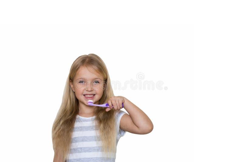 Stående av den gulliga lilla flickan med blont hår som rengörande tand med borsten och tandkräm som isoleras på vit bakgrund arkivbilder