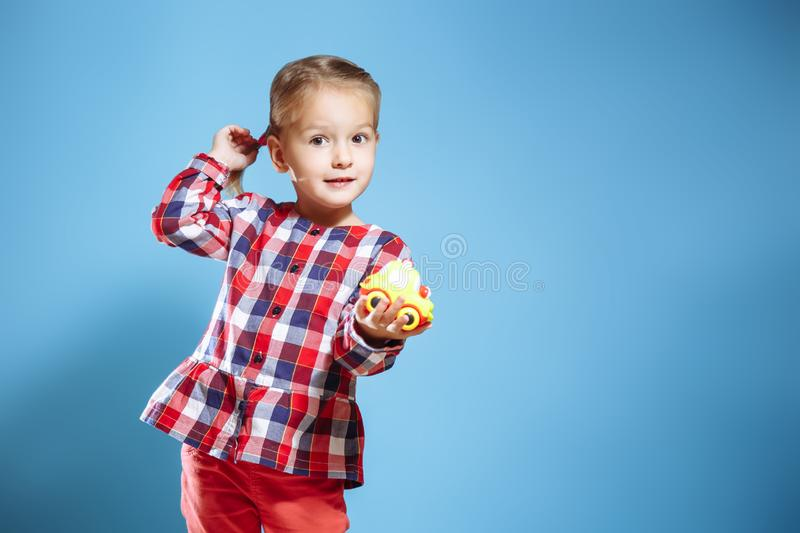 Stående av den gulliga lilla flickan med leksaken på blå bakgrund royaltyfri fotografi