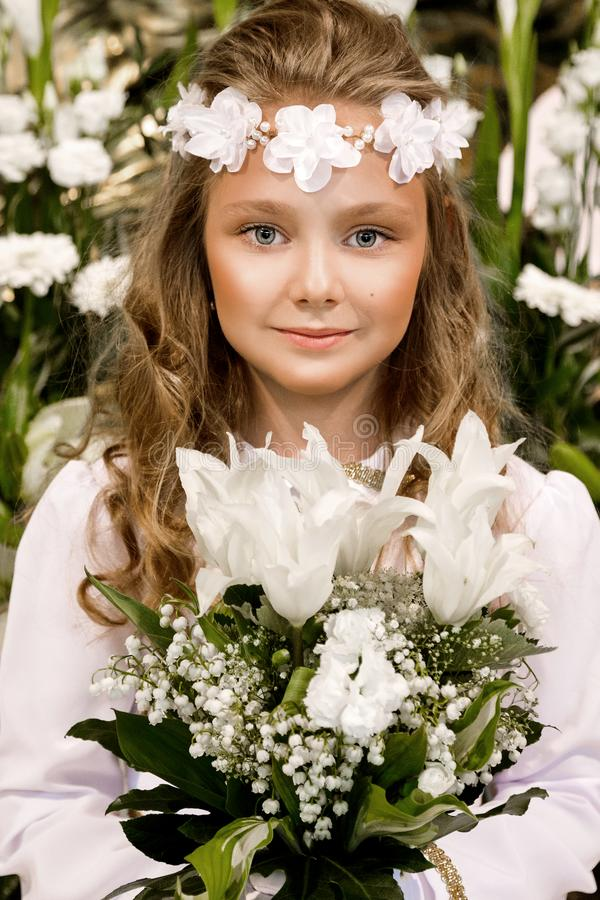 Stående av den gulliga lilla flickan på den vita klänningen och kransen på den kyrkliga porten för första bakgrund för helig natt royaltyfria bilder