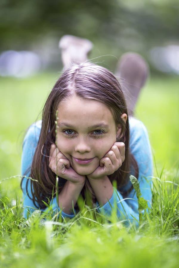 Stående av den gulliga lilla flickan som ligger i grönt gräs Lyckligt arkivfoto