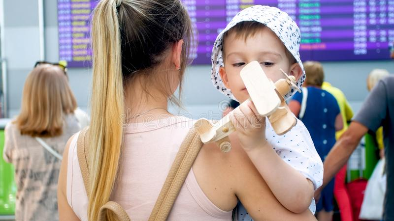 Stående av den gulliga litet barnpojken som spelar med leksakflygplanet och barnmodern i terminal för internationell flygplats arkivbilder