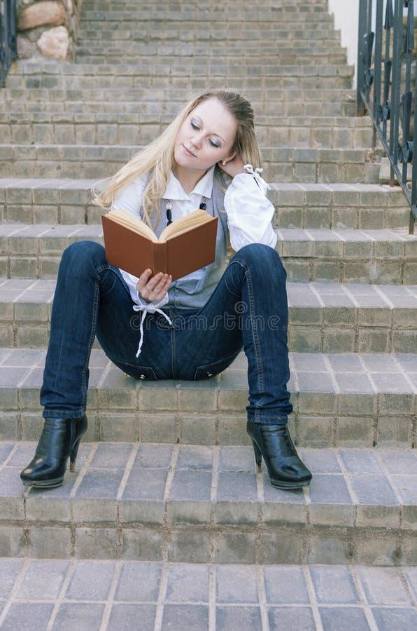 Stående av den gulliga och stillsamma Caucasian blonda kvinnaläseboken, medan sitta raksträcka på trappa utomhus royaltyfri bild
