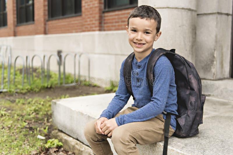 Stående av den gulliga pojken med skola för ryggsäck förutom royaltyfri bild