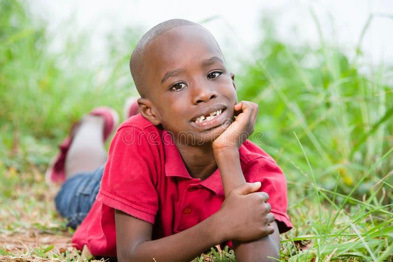 Stående av den gulliga pojken som ligger på nytt grönt gräs royaltyfria bilder