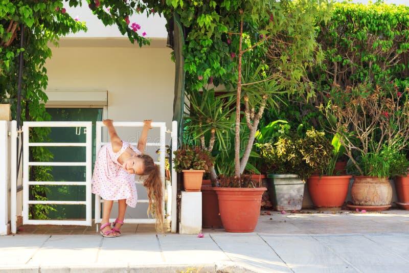 Stående av den gulliga preteenflickan som kopplar av på trädgården på sommardag fotografering för bildbyråer