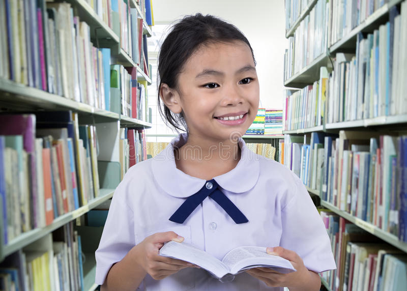 Stående av den gulliga skolflickan som ler, medan läsa arkivbild