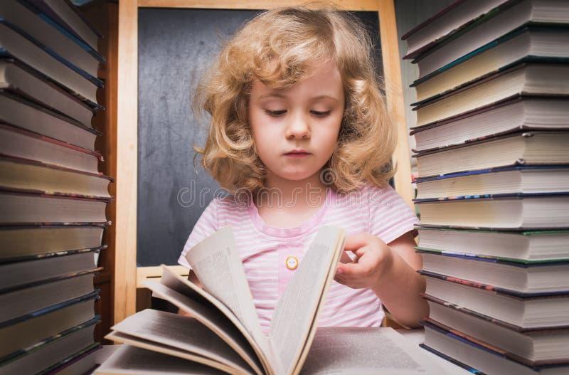 Stående av den gulliga smarta flickan som läser en bok arkivfoto