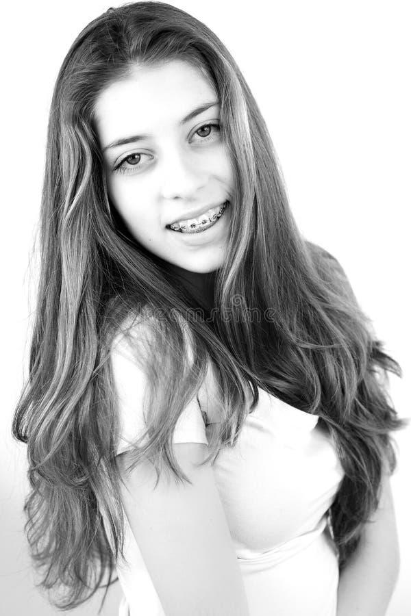 Stående av den gulliga tonåringen med mycket långt le för hår royaltyfri foto