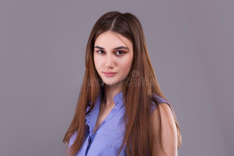 Stående av den gulliga trendiga unga brunettkvinnan i blå skjorta royaltyfria foton