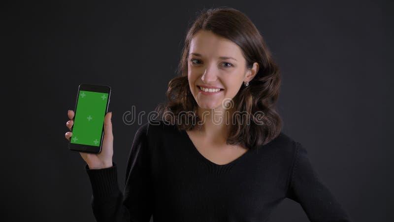 Stående av den gulliga unga brunettkvinnan som joyfully visar den gröna skärmen av smartphonen på svart bakgrund royaltyfria foton
