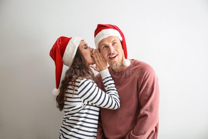 Stående av den gulliga unga kvinnan i jultomtenhatten som berättar hemlighet till hennes pojkvän på vit bakgrund royaltyfri fotografi