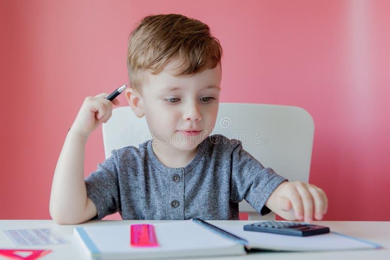 Stående av den gulliga ungepojken hemma som gör läxa Litet koncentrerat barn som skriver med den färgrika blyertspennan, inomhus  royaltyfria foton