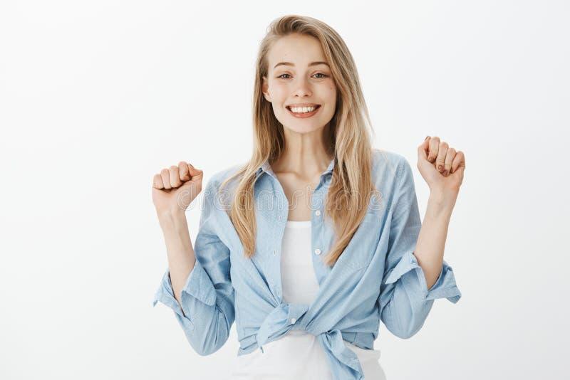 Stående av den gulliga upphetsade europeiska kvinnliga studenten med blont hår som lyfter grep hårt om nävar och glatt ler och at arkivfoto