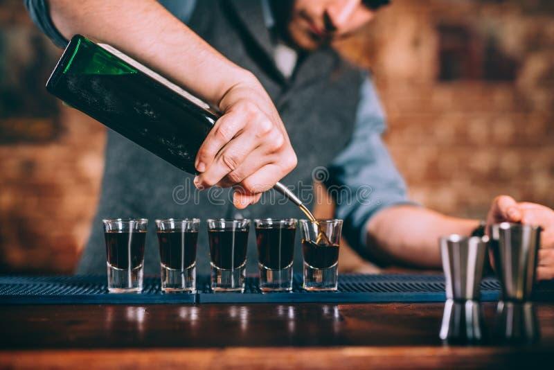 Stående av den hällande alkoholisten för yrkesmässig bartender i skottexponeringsglas på stången arkivbild