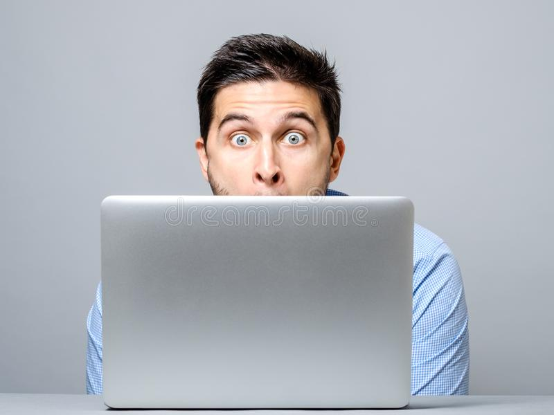 Stående av den häpna mannen med bärbar datordatoren arkivbilder