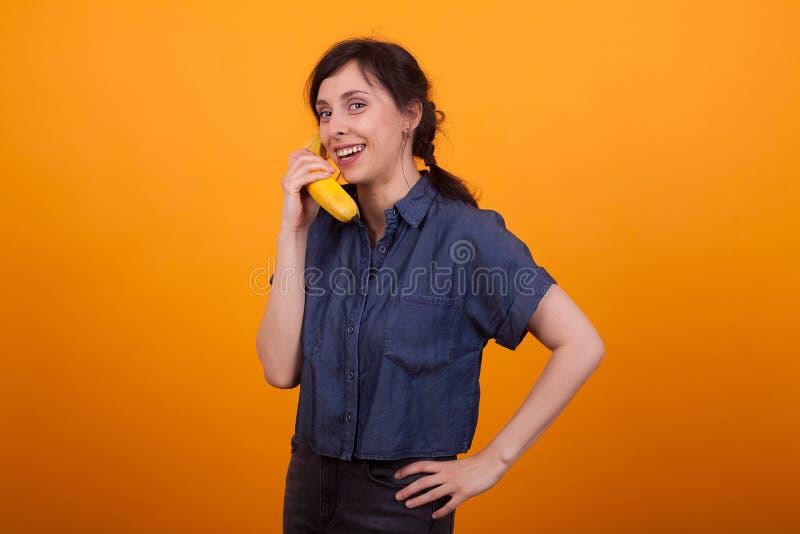 St?ende av den h?pna unga kvinnan som rymmer ny bananfrukt i studio ?ver gul backgroud arkivfoton