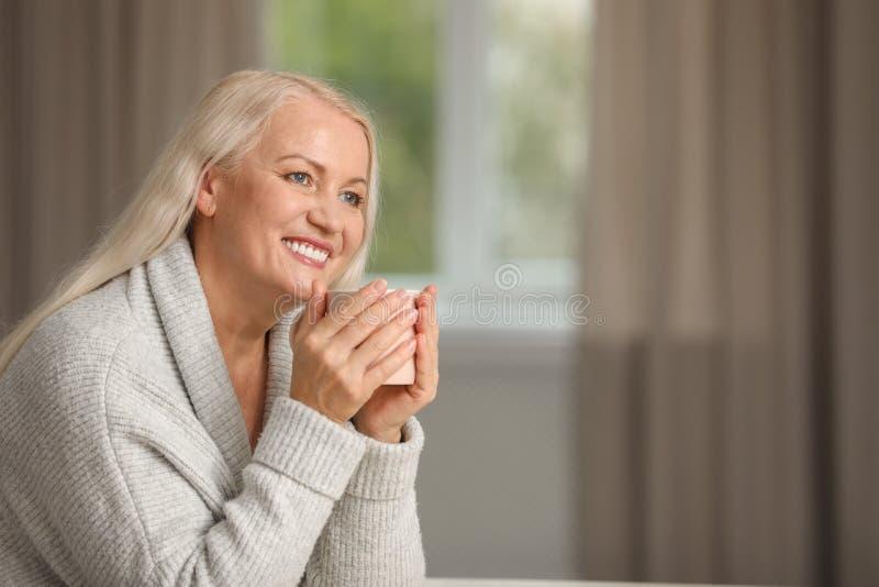 Stående av den härliga äldre kvinnan med kopp te mot suddig bakgrund arkivfoton