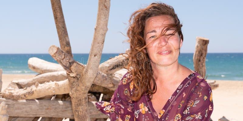 Stående av den härliga 40-åriga brunettkvinnan på drivved för sommarsandstrand i mallrengöringsdukbaner arkivbild