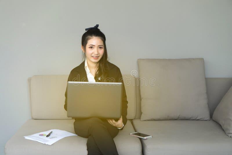 Stående av den härliga affärskvinnan på svart dräkt genom att använda en lapto arkivfoton