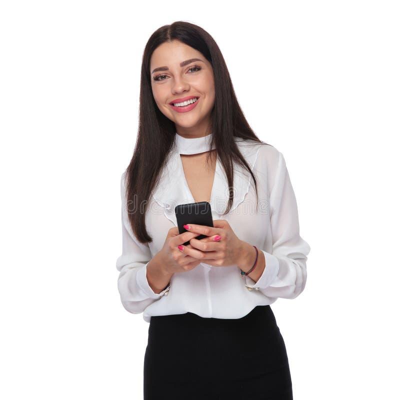 Stående av den härliga affärskvinnan som överför ett textmeddelande royaltyfria foton