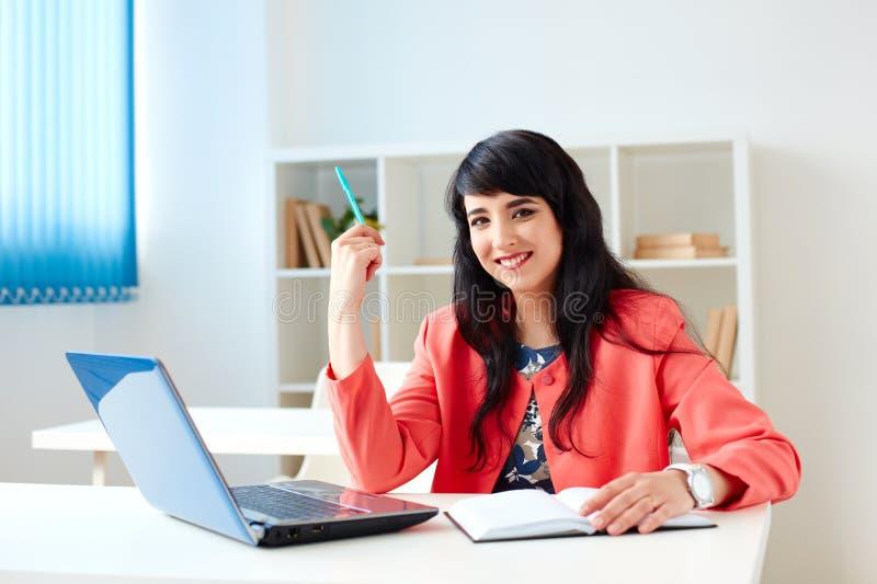 Stående av den härliga affärskvinnan som arbetar på hennes skrivbord med bärbara datorn royaltyfria foton