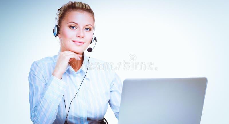 Stående av den härliga affärskvinnan som arbetar på hennes skrivbord med hörlurar med mikrofon och bärbara datorn arkivbilder