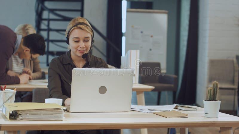 Stående av den härliga affärskvinnan som arbetar på hennes skrivbord med hörlurar med mikrofon och bärbara datorn arkivfoto